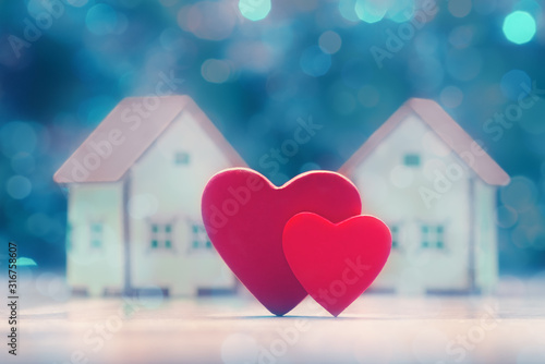 Obraz Two hearts and house models over defocused lights. Valentine's day concept - fototapety do salonu