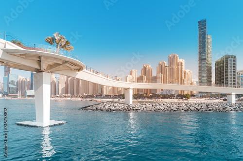 Stampa su Tela Pedestrian Footbridge at the Dubai Marina harbor with various residential buildi