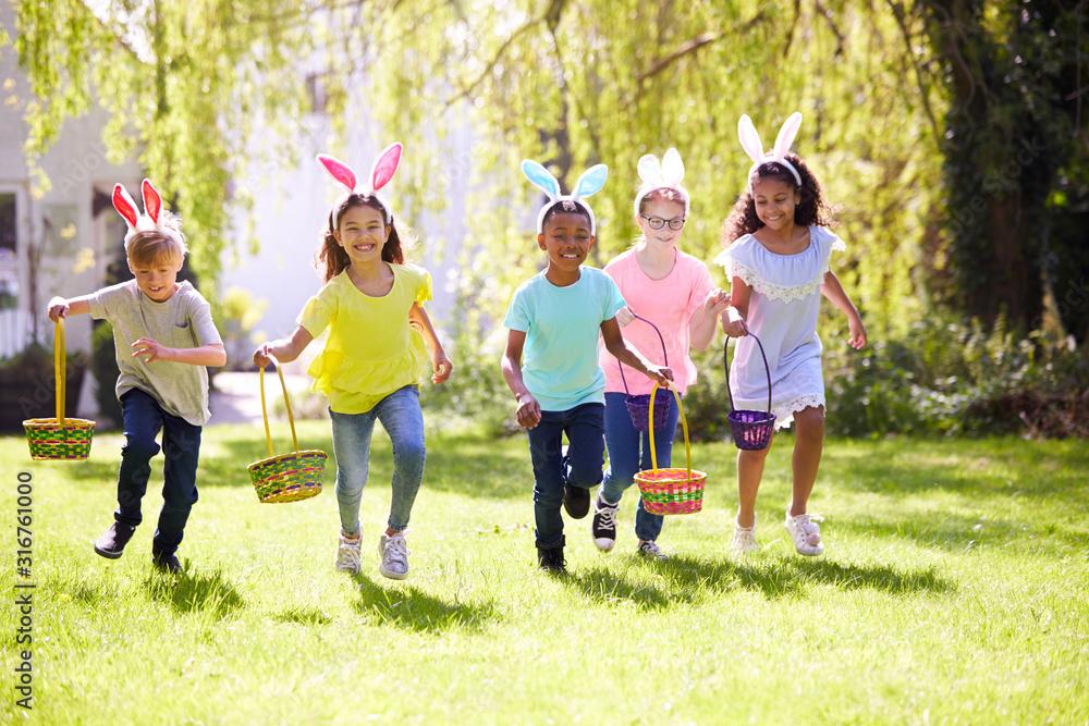 Fototapeta Group Of Children Wearing Bunny Ears Running To Pick Up Chocolate Egg On Easter Egg Hunt In Garden