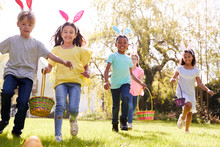 Group Of Children Wearing Bunny Ears Running To Pick Up Chocolate Egg On Easter Egg Hunt In Garden