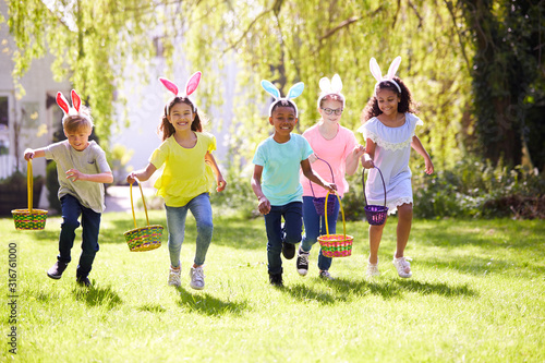 Fotografiet Group Of Children Wearing Bunny Ears Running To Pick Up Chocolate Egg On Easter