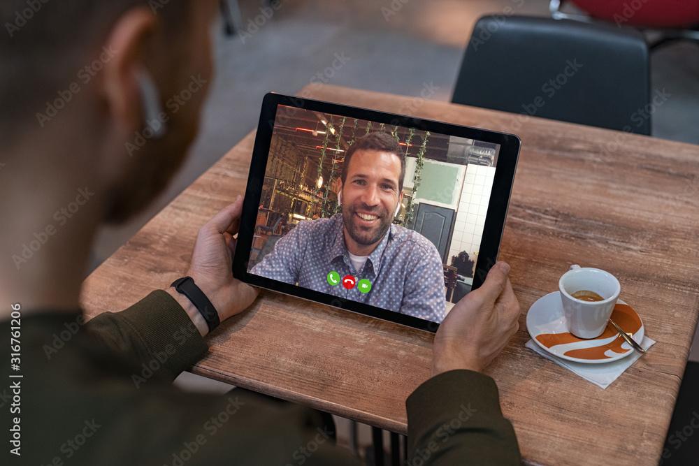 Fototapeta Man doing video call on tablet