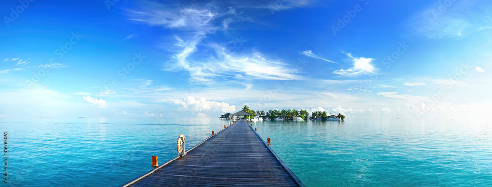 Fototapeta Beautiful tropical landscape background, concept for summer travel and vacation. Wooden pier to an island in ocean against blue sky with white clouds, panoramic view.