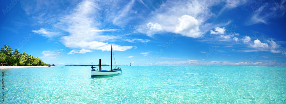 Fototapeta Boat in turquoise ocean water against blue sky with white clouds and tropical island. Natural landscape for summer vacation, panoramic view.