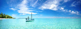 Fototapeta Fototapety z morzem do Twojej sypialni - Boat in turquoise ocean water against blue sky with white clouds and tropical island. Natural landscape for summer vacation, panoramic view.