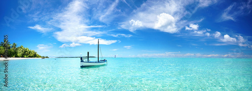 Fototapeta Boat in turquoise ocean water against blue sky with white clouds and tropical island
