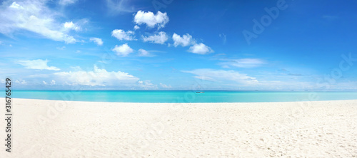 Fototapeta Beautiful beach with white sand, turquoise ocean and blue sky with clouds in sunny day. Panoramic view. Natural background for summer vacation. obraz