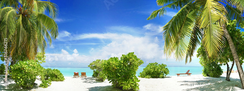 Beautiful tropical beach with white sand, palm tree, beach sunbeds turquoise ocean on  background blue sky with clouds on sunny summer day Poster Mural XXL