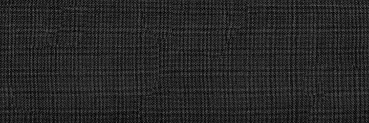 Panoramic close-up texture of natural weave cloth in dark and black color. Fabric texture of natural cotton or linen textile material. Black fabric wide background.