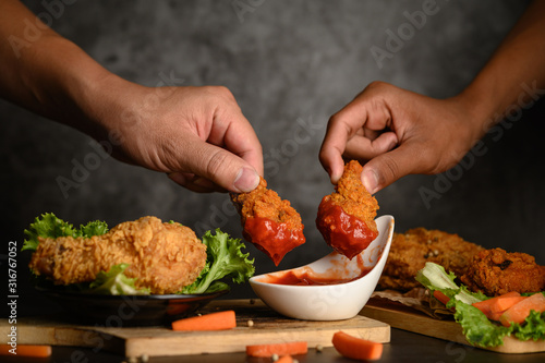 Photo Two hand holding crispy fried chicken dipped in tomato sauce