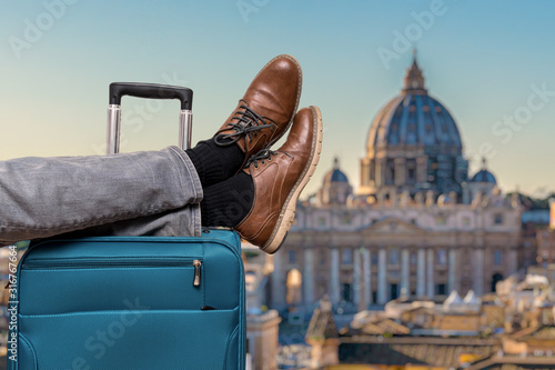 Tourist has legs on suitcase and relaxing in Rome.