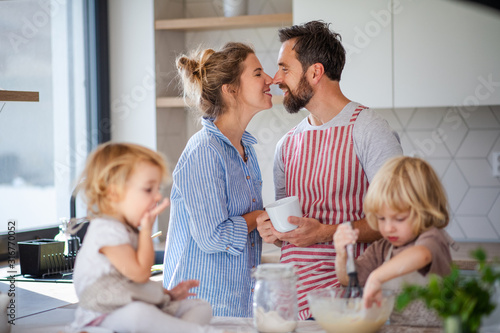 Young family with two small children indoors in kitchen, cooking.
