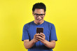 Leinwanddruck Bild - Shocked face of Asian man in blue shirt looking at phone screen on yellow