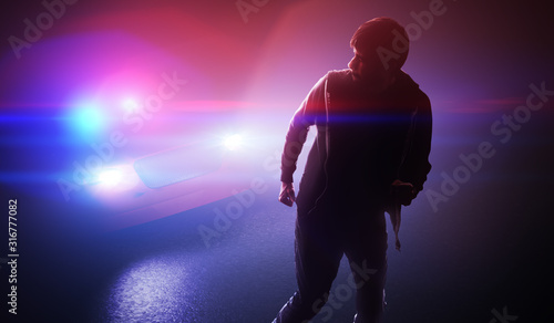 Silhouette of young man - thief escaping from police car at night Wallpaper Mural