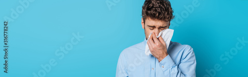 panoramic shot of diseased man sneezing in paper napkin on blue background Canvas-taulu