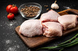canvas print picture - Raw chicken thigh on black background.