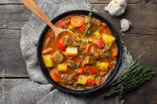 Fototapeta Goulash, beef stew or bogrash soup with meat, vegetables and spices in cast iron pan on wooden table. Hungarian cuisine. Rustic style. Top view. obraz