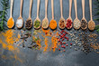 Colourful various herbs and spices in spoons for cooking on dark background