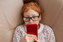 Red-haired Little Girl With Glasses Talking On The Phone