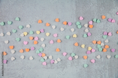 Valentine's Day gray cement background with pastel colored conversation heart ca Wallpaper Mural