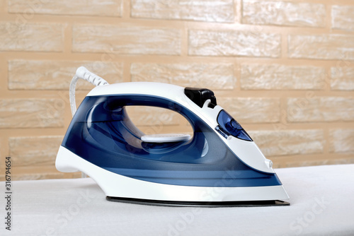 Fotografía New modern electric steam iron on ironing board