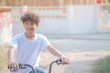 A beautiful boy rides a bicycle along his house