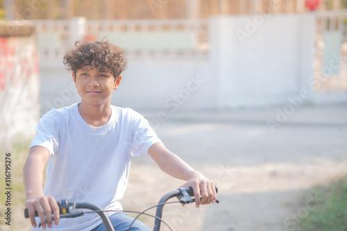 Fototapeta A beautiful boy rides a bicycle along his house obraz na płótnie