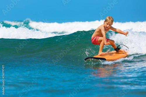 Happy boy - young surfer learning ride, jump from surfboard with fun, run to beach Canvas Print