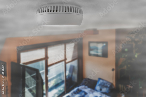 Obraz Domestic smoke alarm / battery powered smoke detector on the ceiling in room filled with smoke from fire at home - fototapety do salonu