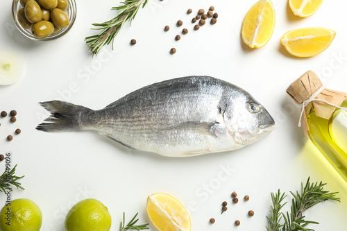 Fototapeta Fresh Dorado fish, spices and cooking ingredients on white background, top view obraz