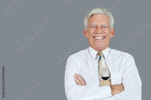 Fototapeta Portrait of cheerful senior businessman with arms crossed over gray background