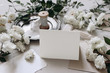 canvas print picture - Wedding table composition. Place card mockup scene.with fading white rose flowers, silver plate, silk ribbons and envelopes. Grey background, selective focus. Moody festive, celebration concept.