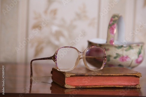 Fotografija Spectacles on hardbacked book with china bowl