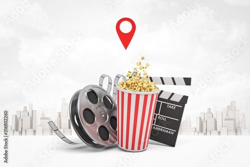 Obraz 3d rendering of popcorn bucket, film reel, movie clapper on white city skyscrapers background - fototapety do salonu