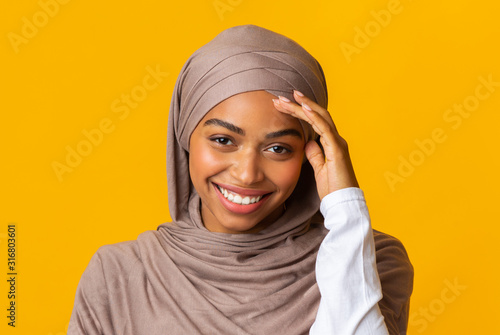 Canvastavla  Smiling afro muslim girl in headscarf shyly looking at camera