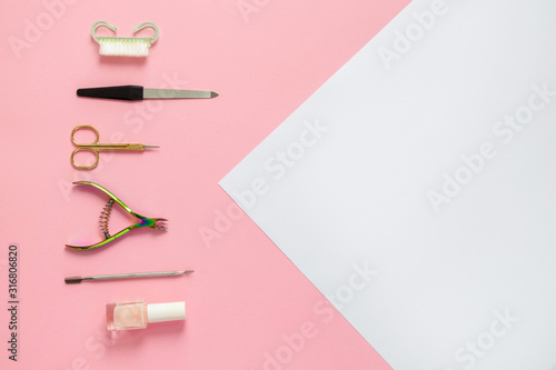A set of cosmetic tools for manicure and pedicure on a pink and white background