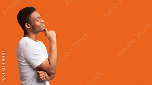 Obraz Pensive afro man profile portrait on orange background - fototapety do salonu
