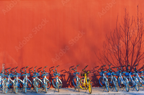 Beijing, China-31 December 2019, Row of share bikes parking on footpath with red wall in Beijijng city, China Wallpaper Mural