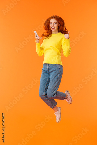 Vertical full-length shot carefree, excited and pleased good-looking ginger girl Tableau sur Toile