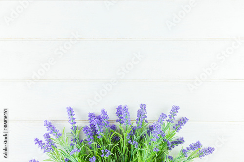 Violet Flowers of Lavender, top view on white Wooden background.