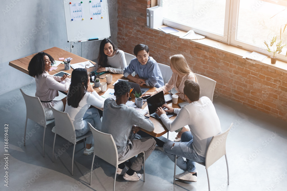 Fototapeta Creative international team discussing new project in modern office