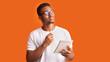 Pensive afro man portrait on orange background