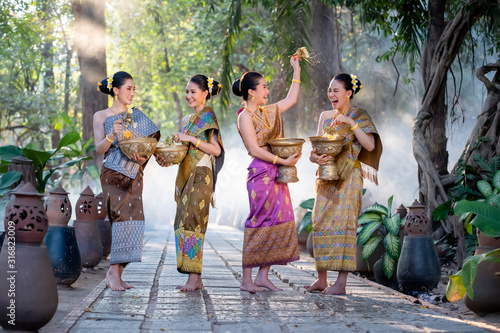Obraz Beautiful Asian woman splashing water during tradition festival Thai,Songkran festival. - fototapety do salonu