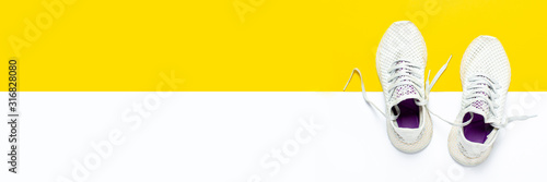 Fotografia White running shoes on an abstract yellow-white background