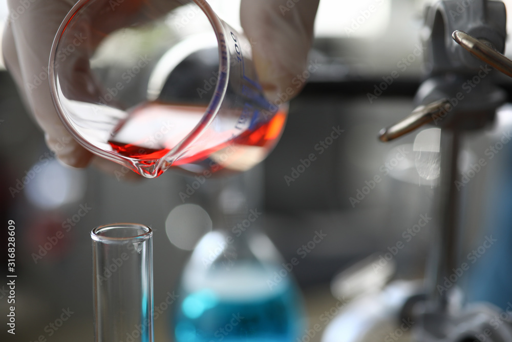 Fototapeta Close-up of assistant hand holding flask. Chemist pouring red liquid into vial. Researcher making mixture of fluid for experiment in lab. Chemical experiments concept