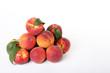 Leinwanddruck Bild Fresh peaches with green leafs on white wooden table