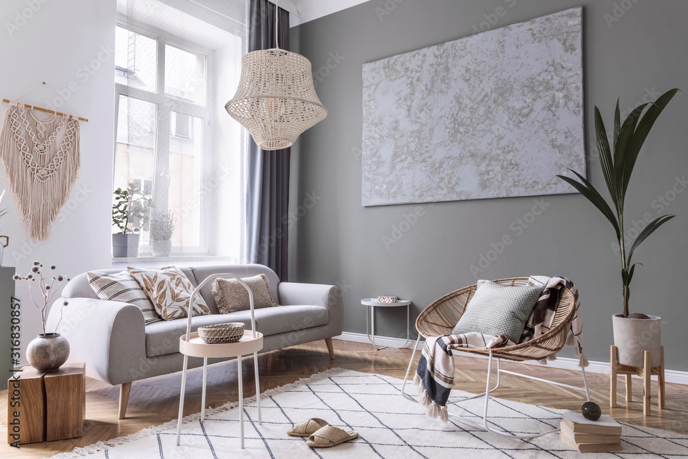 Fototapeta Modern boho interior design of living room with design rattan armchair, gray sofa, coffee table, beige macrame, plants and elegant accessories. Stylish home decor. Abstract paintings. Template.