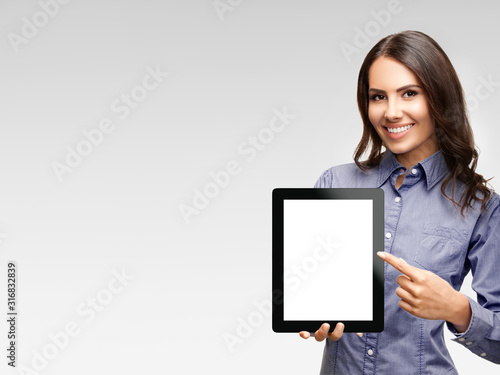 Obraz Happy smiling attractive businesswoman showing blank tablet pc monitor, with copy space area for some text, advertising or slogan, over grey background - fototapety do salonu