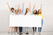 Group Of Women Holding Blank Poster Posing Near Wall Indoor