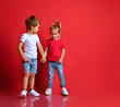 Leinwanddruck Bild - Small happy children boy and girl in stylish casual clothing standing, holding hands and feeling shy over red background